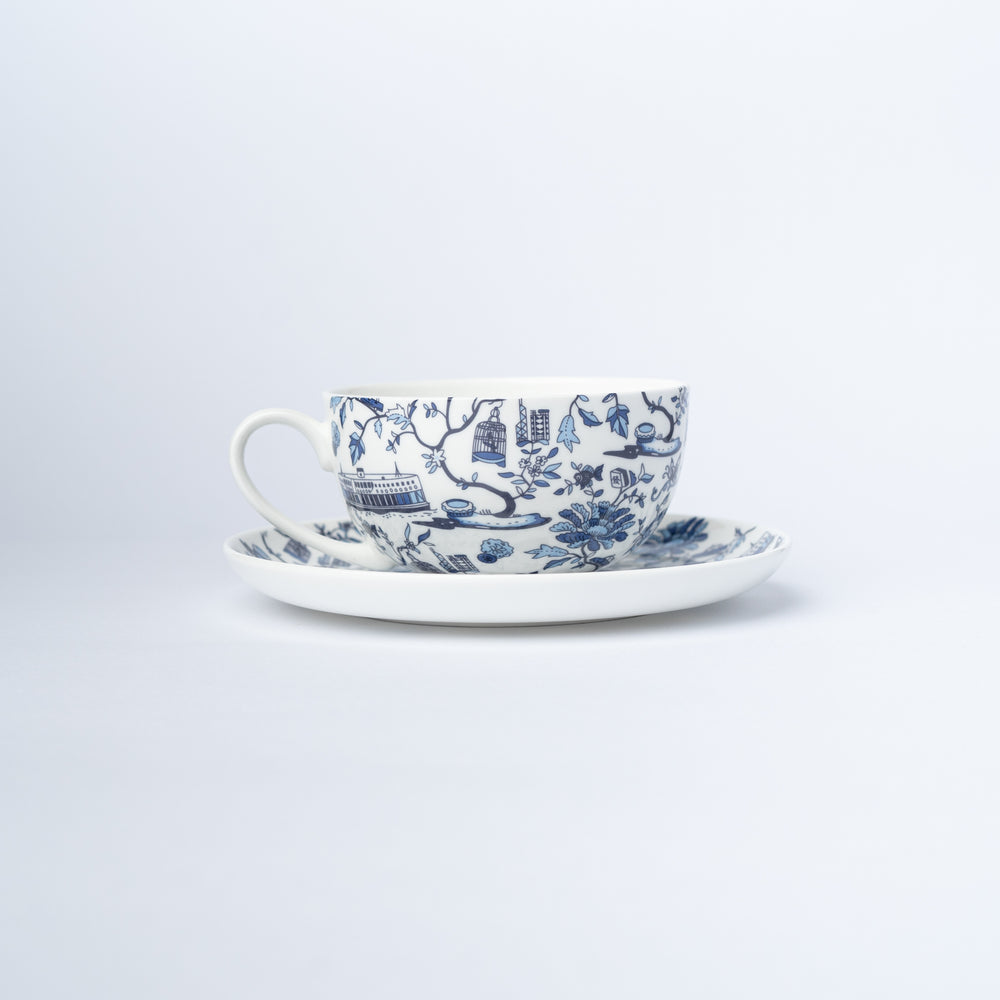 A cup and saucer with a blue and white design of iconic Hong Kong imagery.