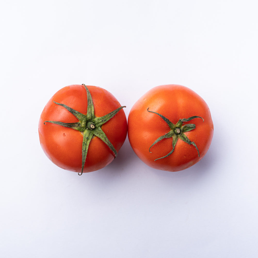 Two red tomatoes with green tops.