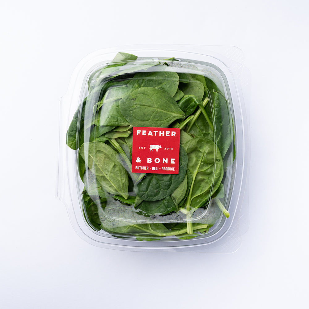 A plastic box of spinach leaves with a square red Feather & Bone label.