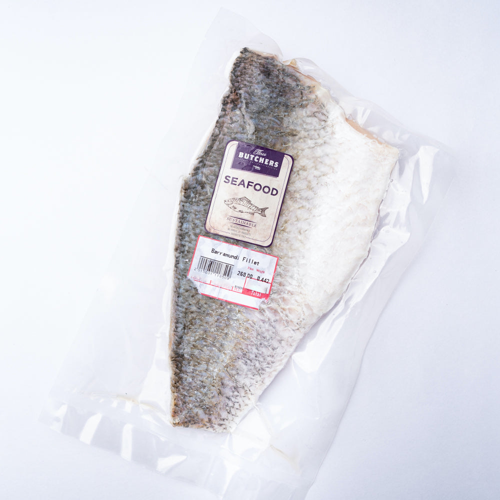A frozen Barramundi Fillet with the silvery skin on in a vacuum bag with a purple label saying Three Butchers Fish.