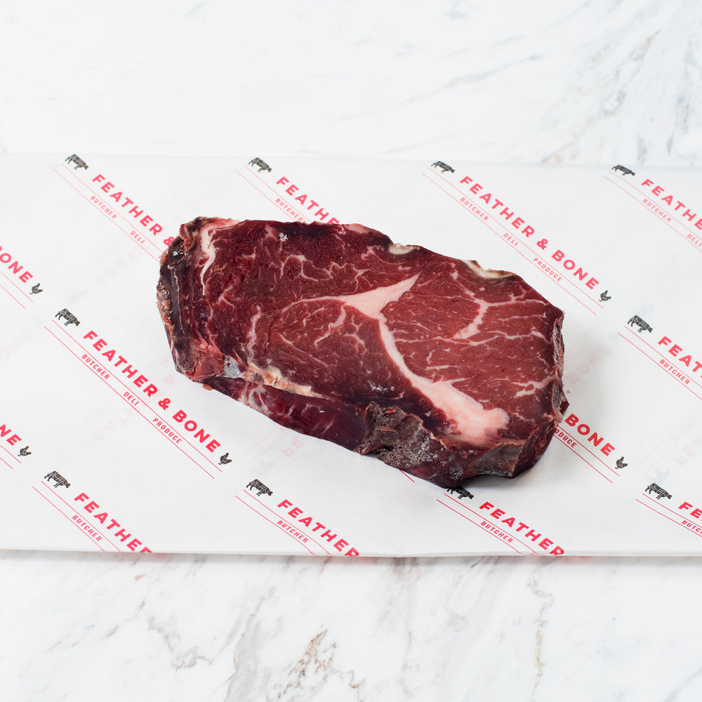 A Dry Aged Grain Fed Ribeye beef steak.