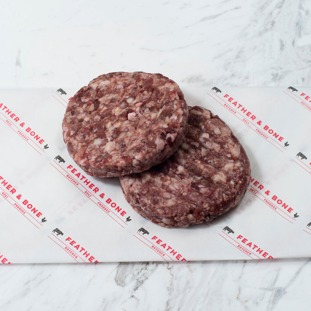 Two dry aged beef patties on Feather & Bone branded paper.