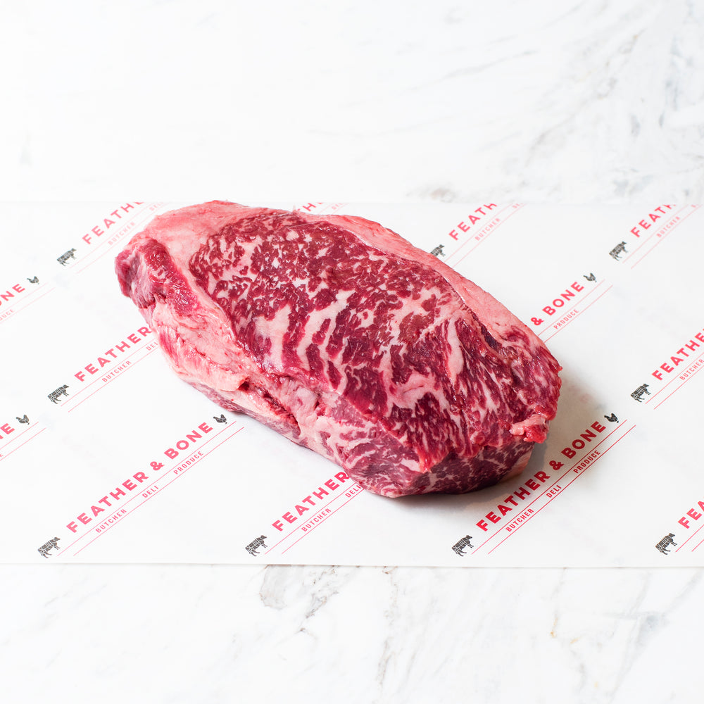 A Wagyu Sirloin MBS7 beef steak on a marble slab.