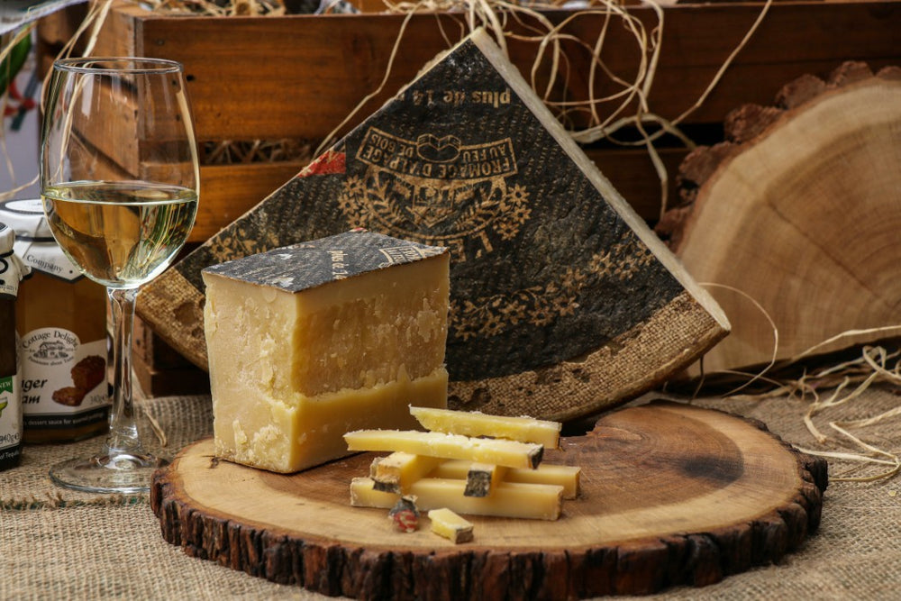 A crumbled wedge of L'Etivaz cheese on a rustic wooden board.