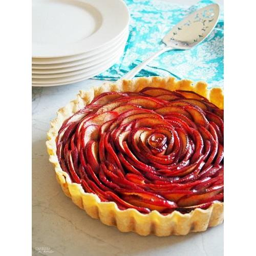 A tarte shell with ornate sliced red apple.