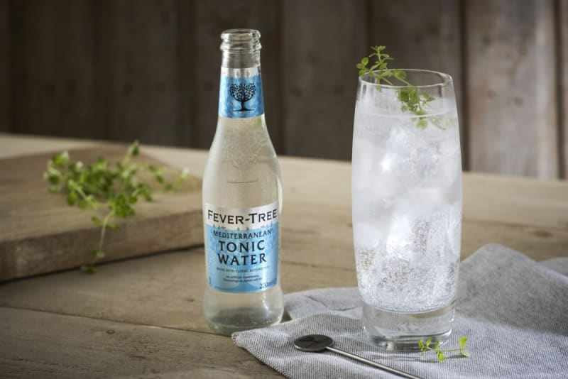 A bottle and a glass of Fever Tree Mediterranean Tonic Water on a wooden table.