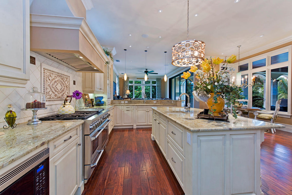 Large Naples Florida Kitchen with white cabinets amazing lighting fixtures chandelier from J Bradwells Home Kitchen & Design