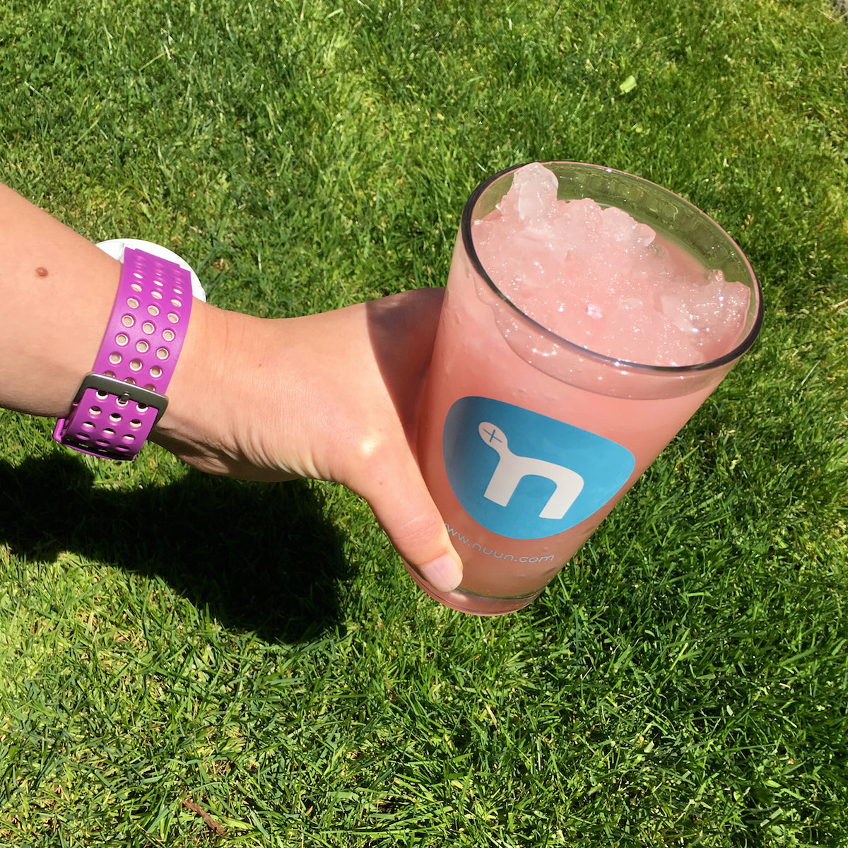 person holding a nuun pint glass with a nuun slushie