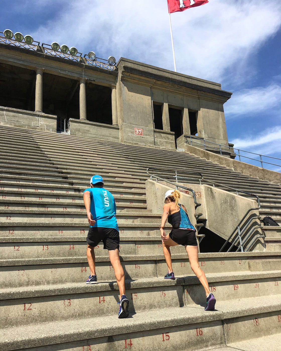 Two people doing a workout running up stairs