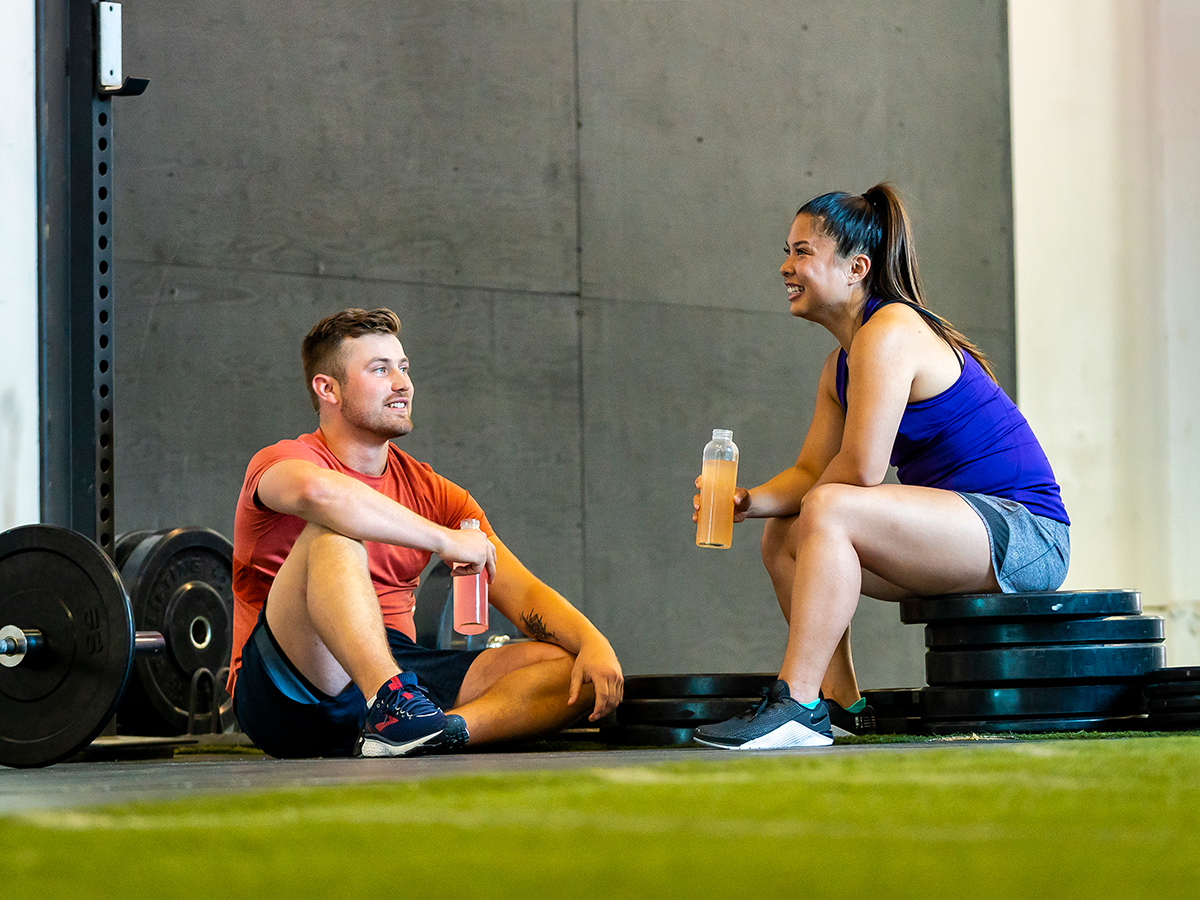 Two people resting and drinking nuun at a gym