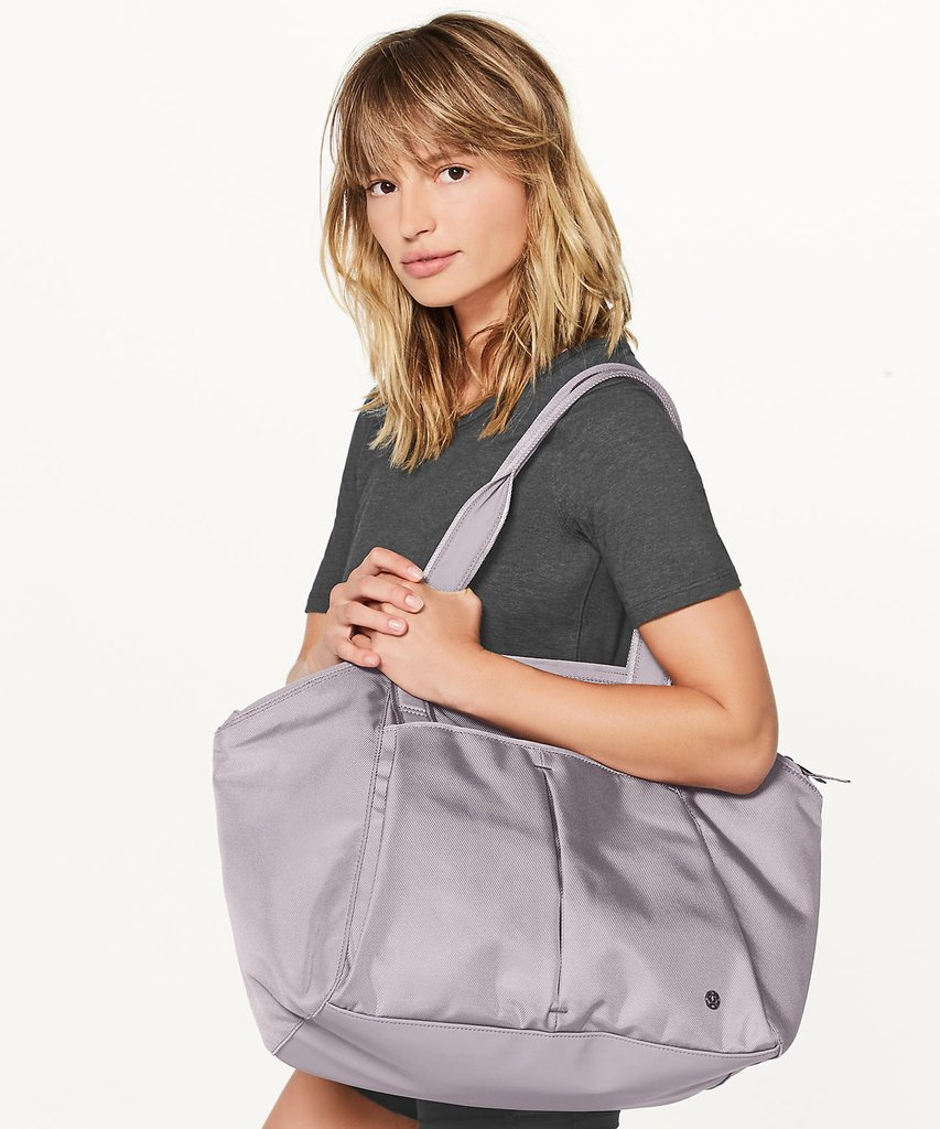 Woman posing with a purple bag