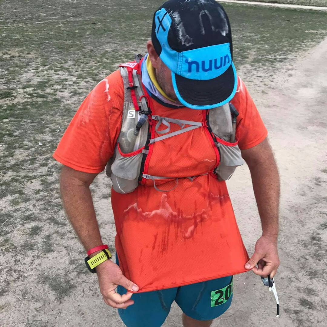 trail runner holding their shirt showing sweat spots after a run