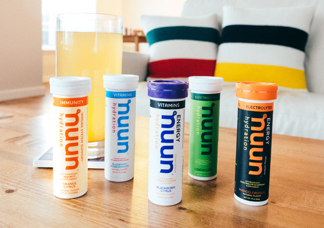 Five nuun hydration tubes with a glass of nuun on a table