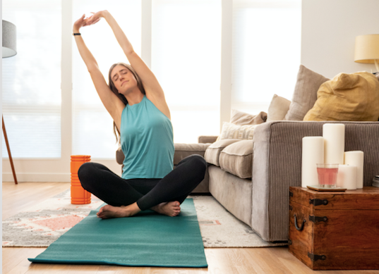 person doing yoga on a mat at home in the living room