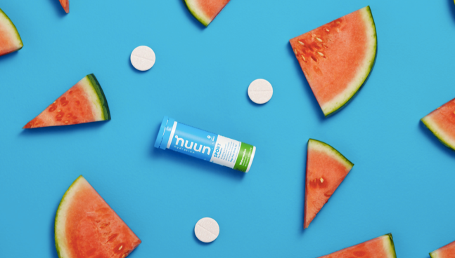 A Nuun Tube on a blue background with slices of watermelon.