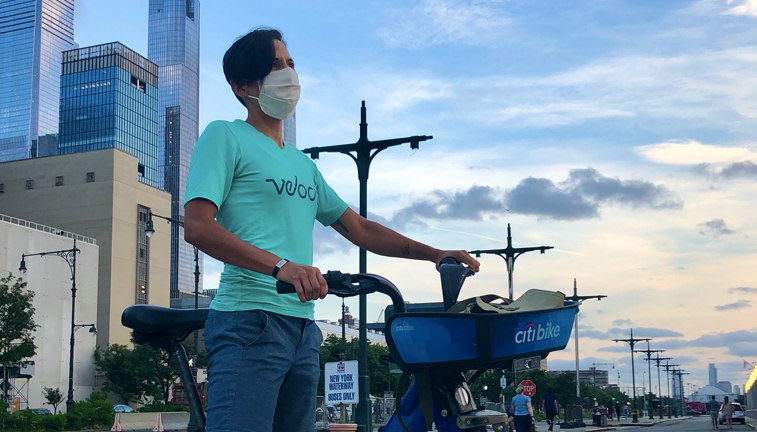 Micah wears a face mask and stands with the citi bike about to embark on a 101 mile ride around New York City