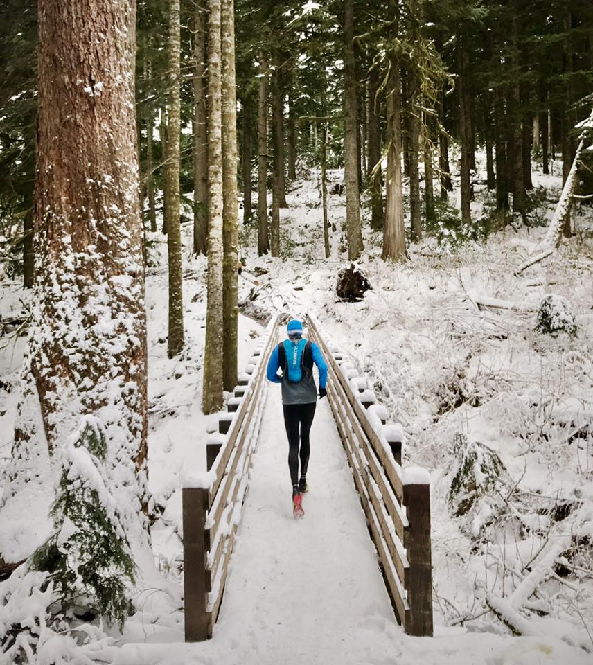 Trail running on a snow covered bridge in winter