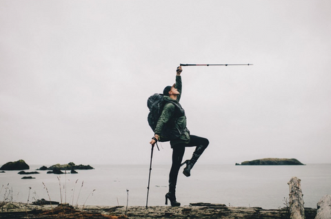 With platform heels and hiking poles, Pattie poses on a driftwood log in front of a vast grey body of water