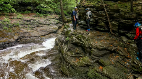 Alyssa and others navigate a rock ledge above a rushing river