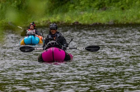 Two adventure racers paddle personal boats along a river