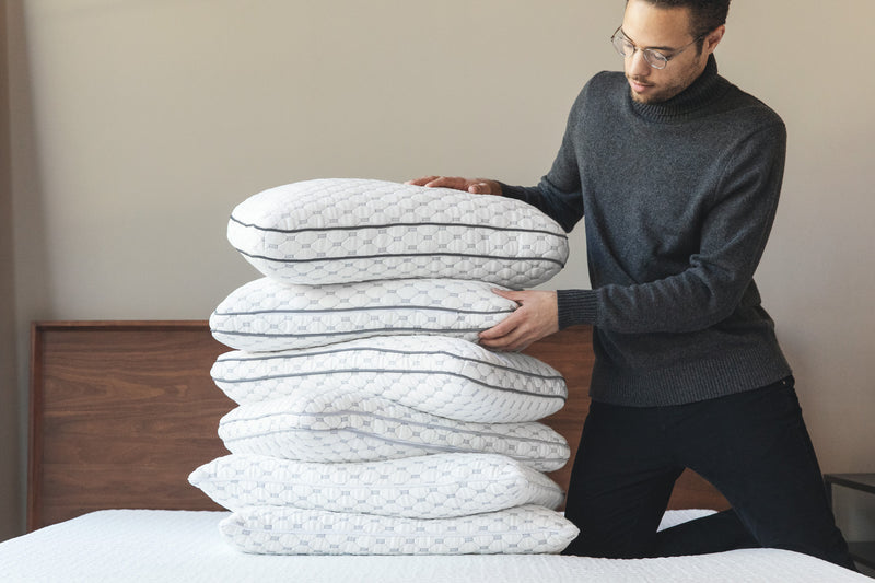Photo of a guy stacking up a pile of Muse pillows