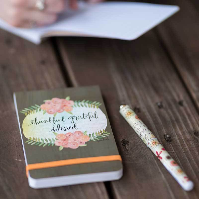 With 136 lined pages and elastic band closure, our Thankful Grateful Blessed Pocket Notepad features a sweet floral wreath design and affirming inspirational message from artist, Katie Doucette.