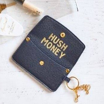 Hush Money Credit Card Pouch is accented with double ring, fashionable carabiner, brand charm, snap & brads in glistening gold - perfectly matched to the embossed, interior sentiment: HUSH MONEY