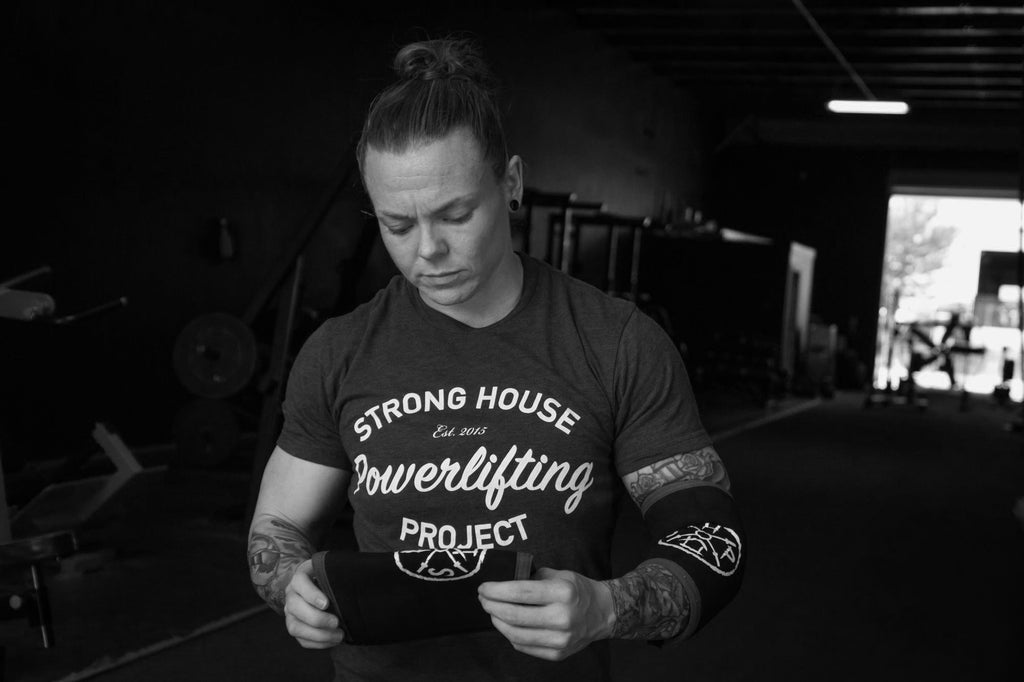 "Stacy ""Bama"" Burr inspecting a pair of StrongHouse Project Powerlifting competition elbow sleeves."