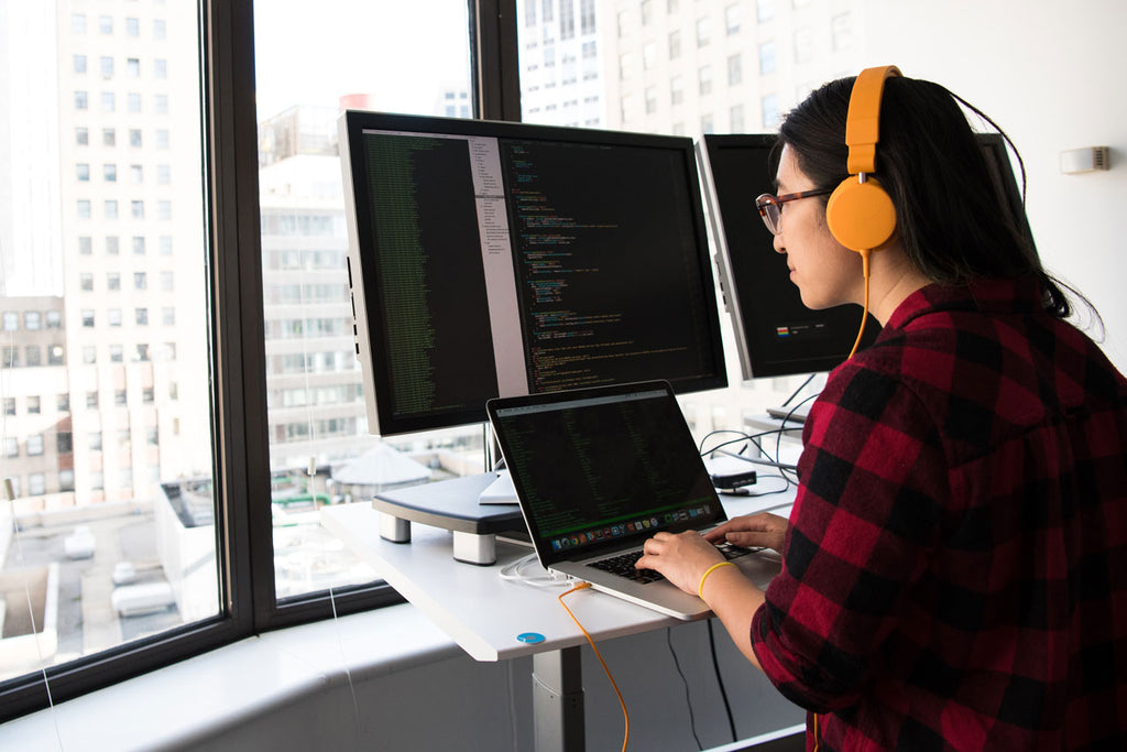 Woman coding on dual screen in office