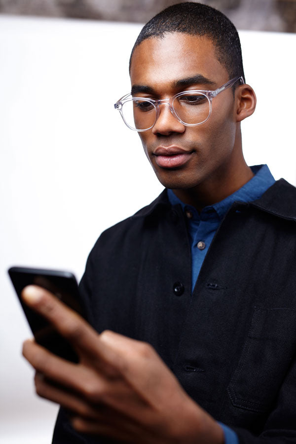 Man looking at smartphone wearing LUMES blue light blocking glasses
