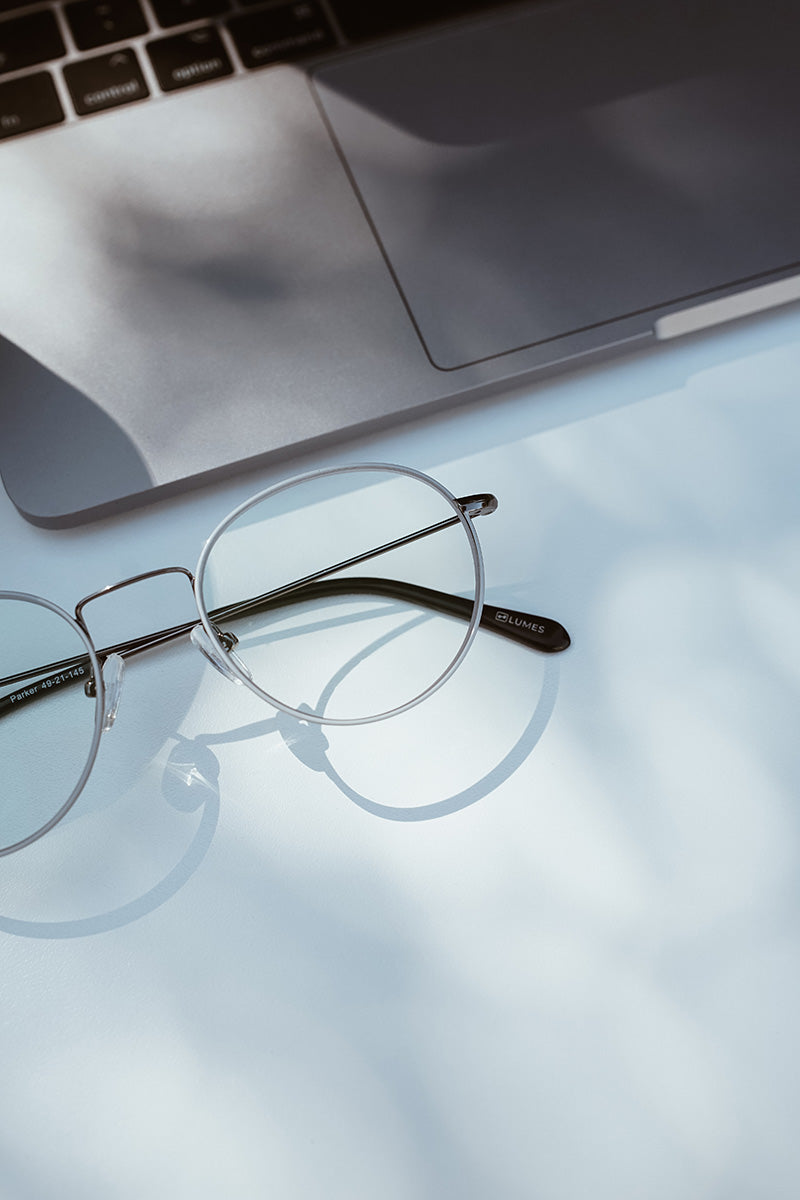 LUMES blue light blocking glasses lying next to laptop on table