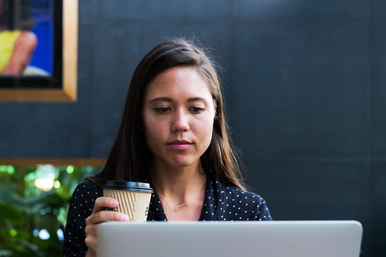 Woman holding coffee looking at laptop screen