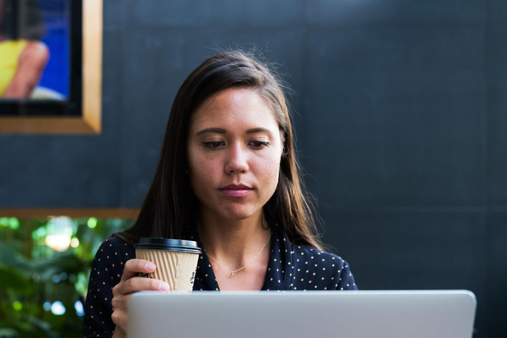 Professional woman with coffee cup looking at screen close up