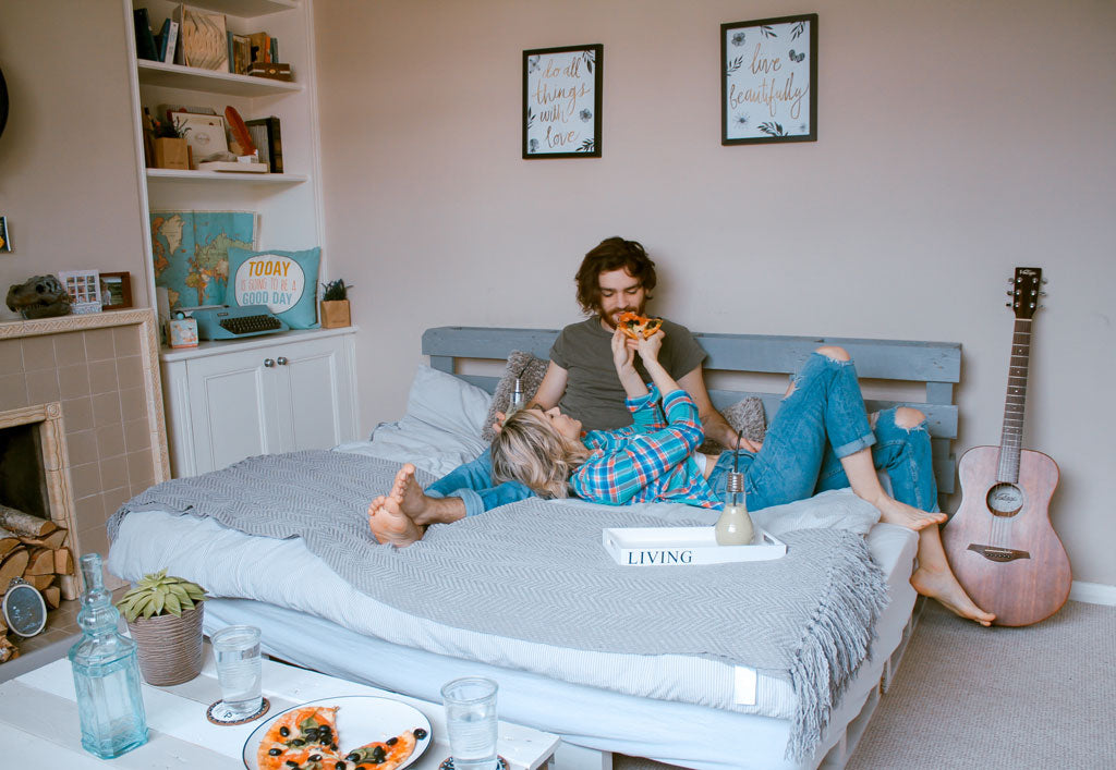 Young couple having fun on bed eating pizza