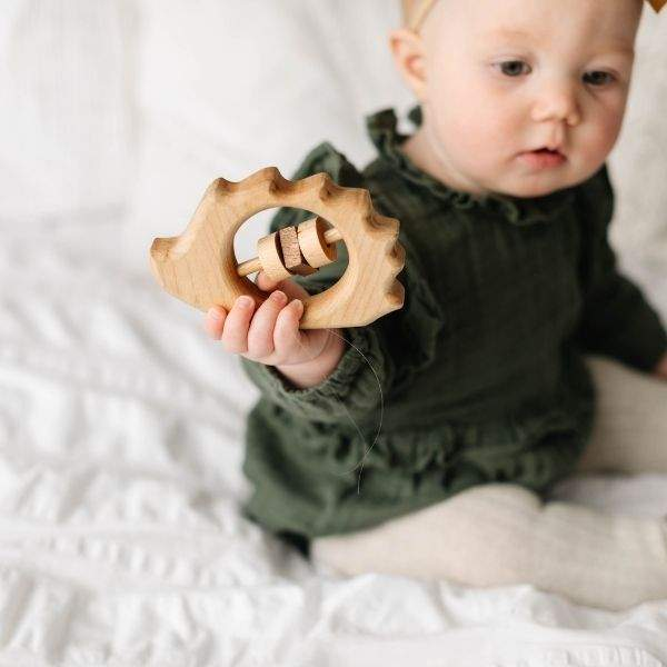 infant holding organic wooden baby rattle shaped like a hedgehog.