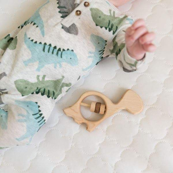 wooden dinosaur baby rattle laying next to infant in a dinosaur outfit.