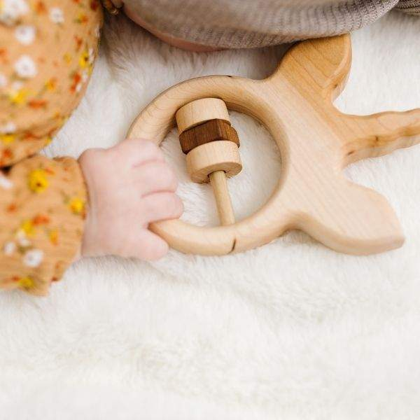 small infant hand holding onto unicorn wooden baby rattle.