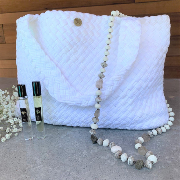 The perfect gift for anyone who loves clean, fresh scents and artisan accessories. Available for a limited time, the Summer Rain Gift Set includes one Bijou Vert 7.5ml rollerball, one Summer Rain 7.5ml rollerball, our exclusive handwoven Paula Coles Tote Bag, and our Haitian Handmade Beaded Necklace