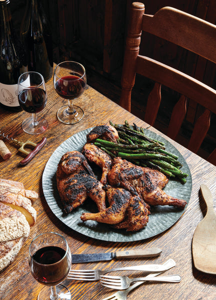 grilled chicken on a plate with asparagus and red in glasses on table with silverware