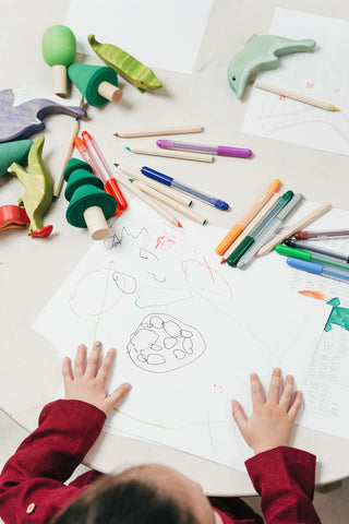 child drawing on a table with art products and wooden toys