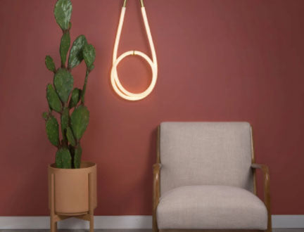 Artistic statement loop light fixture by Color Cord company next to a chair and houseplant