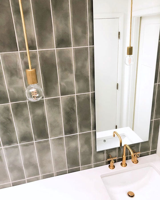 Relaxing lighting for the bathroom with brass hardware, dimmable bulb, and modern finishes.