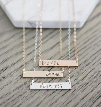 Breathe Bar Necklace, flat lay of three