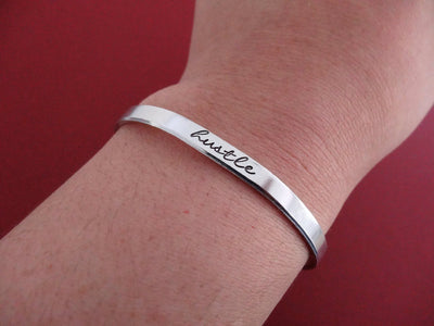 Hustle Bracelet, modeled on wrist with red background