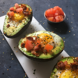 Avocado halves filled with sunny side up egg, tomatoes and bacon
