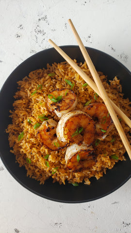 bowl of red smoke rice with honey pepper shrimp on top