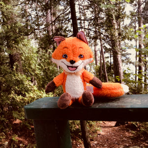 A plush Rocco sitting with a forest in the background