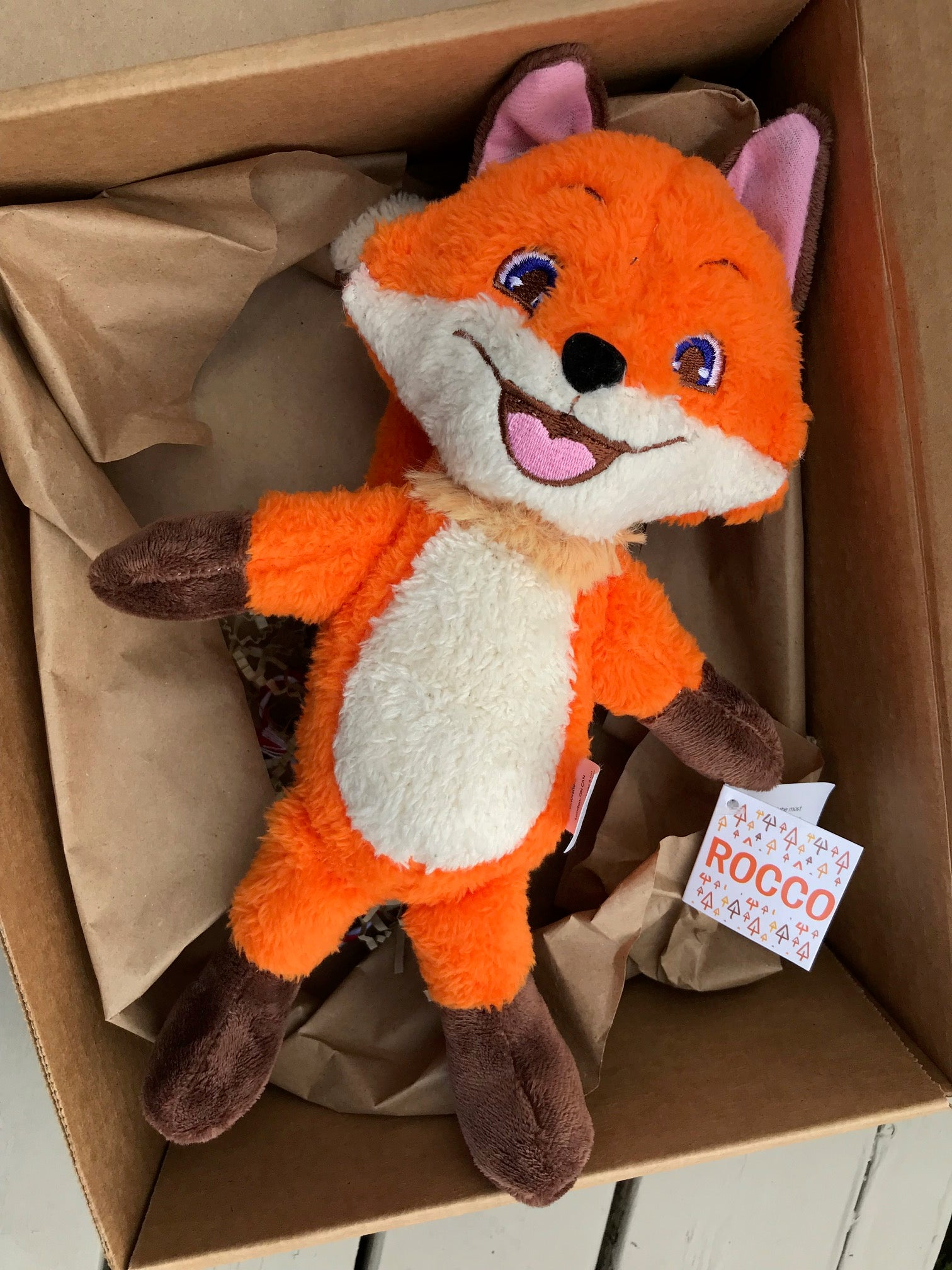 A picture of the Rocco plush fox lying in a gift box