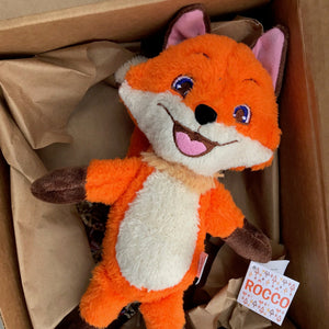 A plush Rocco sitting inside a gift box