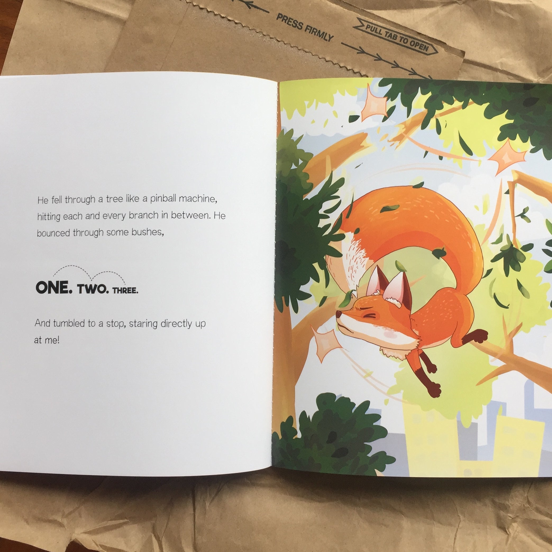 The Hey Rocco storybook opened to a page with an illustrated picture of Rocco falling through a tree